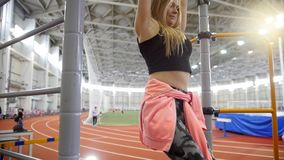 Young woman pulls up on the crossbar in the sports hall. Pumping lower parts of her body