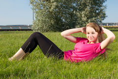 Young woman pumping press in park Stock Photography