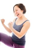 Young woman punching the air and laughing Stock Photo