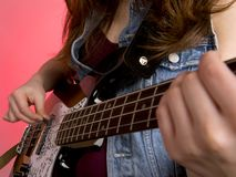 Young woman punk woman playing bass guitar Stock Images