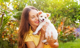 Young woman with a puppy dog. Young smiling woman hugging cute little puppy outdoor royalty free stock images