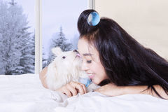 Young woman with puppy licking her face. Image of pretty young woman lying on the bed with puppy licking her face in winter season Stock Photos