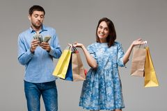 Young woman with purchases, man holding money over grey background. Royalty Free Stock Photos