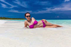 Young woman in purple bikini covered lying sand on the beach Royalty Free Stock Photography