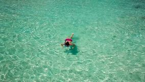 Young woman swimming in a coral lagoon. Young woman in purple bikini swimming in a coral lagoon stock video footage