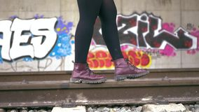 Young woman with purple boots and black leggins keeps her balance walking along the train tracks. In the background. Tunnel full of graffiti. Slow motion stock footage