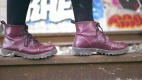 Young woman with purple boots and black leggins keeps her balance walking along the train tracks. In the background, tunnel full of graffiti. Slow motion stock video footage