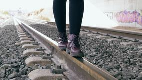 Young woman with purple boots keeps her balance walking along the train tracks. In the background, tunnel full of graffiti. Slow motion. Travel, danger stock footage