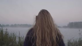 A young woman walks toward the lake and her long hair sways in the wind stock video