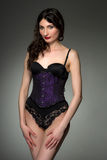 Young woman in purple corset and black lingerie Stock Photo