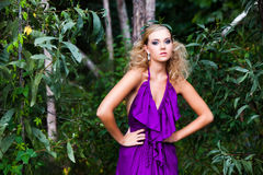 Young Woman in a Purple Dress Outdoors Royalty Free Stock Photos