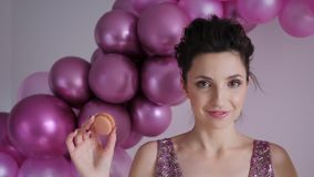 A young woman in a purple dress puts a round cookie. Young woman in a purple dress puts a round cookie to her eyes stock footage