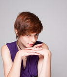 Young woman in purple dress putting on makeup Stock Photos