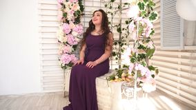 Young woman in purple dress sits on wedding bench with flowers. Dolly shot stock video