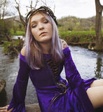 Young woman in purple gown sitting by a river Royalty Free Stock Photos