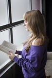Young Woman in a Purple Shirt Reading a Book Royalty Free Stock Images
