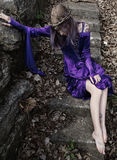 Young woman in purple velvet gown and twig crown sitting on stone stairs by wall. Royalty Free Stock Image