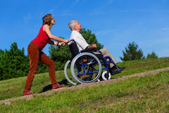 Young woman push the old man on wheelchair to the top of the hil Stock Image