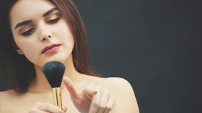 A young woman pushes a brush with his hand. The skin flies over a black background. Cropped image. Makeup application in