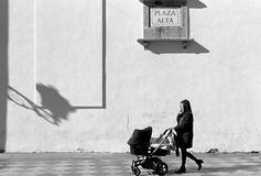 Young Woman Pushing Baby Buggy While Talking on Mobile Phone. A young woman pushing a baby buggy while talking on her cell phone. Plaza Alta, Algeciras Royalty Free Stock Images