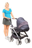Young woman pushing a baby stroller Stock Photography