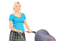 Young woman pushing a baby stroller Stock Image