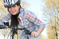 Young woman pushing a bicycle. And wearing a helmet royalty free stock photo