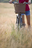A young woman pushing a bicycle through long grass Royalty Free Stock Image