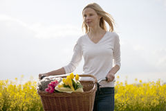 A young woman pushing a bicycle next to a seed field in flower Stock Photo