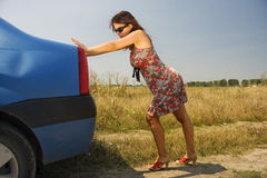 Young woman pushing a car. Young woman pushing a broken car on a countryside road Stock Images