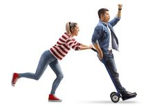 Young woman pushing a hand truck with a young man riding on it Royalty Free Stock Image