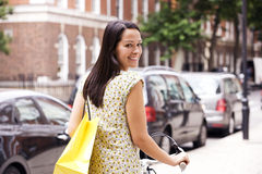 A young woman pushing her bicycle, carrying a shopping bag Royalty Free Stock Photo