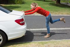 Young woman pushing her broken down car Royalty Free Stock Images