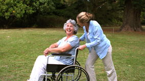 Young woman pushing her mother in wheelchair. In slow motion stock footage
