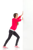Young woman pushing the wall. Full length studio shot isolated on white stock images