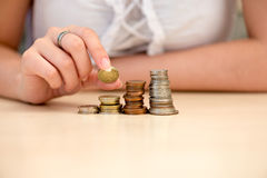 Young woman put coins on coin-stack Stock Images