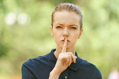 Young woman put finger to lips Royalty Free Stock Images