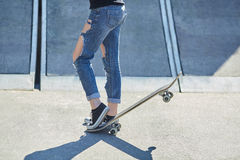 Young woman put her foot on a skateboard Stock Photography