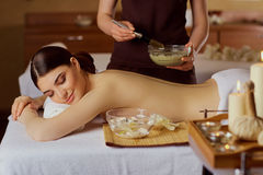 Young woman is put on a mask on her back in  spa salon. Young women is put on a mask on her back in  spa salon Stock Image