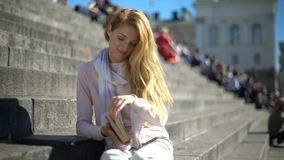 Young woman puts aside the laptop and picks up a book on the stairs in the center of the city stock video footage