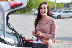 Woman puts bags from the shopping cart to the trunk. Young woman puts bags from the shopping cart to the trunk of a car at the parking Royalty Free Stock Photography