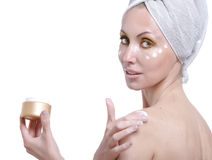 The young woman puts a cosmetic cream on a body stock images