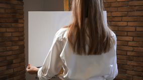 A young woman puts on an easel a drawing canvas. Art Studio. 4K Slow Mo. A young woman puts on an easel a drawing canvas. Art Studio stock footage