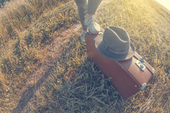 Young woman puts foot on brown vintage suitcase in the field road during summer sunset. Toned image and travel concept Royalty Free Stock Photography