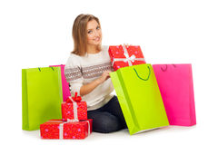 Young woman puts gift in shopping bags Royalty Free Stock Photos