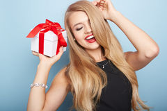 Young woman puts her ear to the present wrapped. Stock Images
