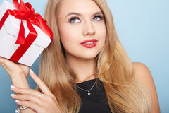 Young woman puts her ear to the present wrapped. Royalty Free Stock Photos