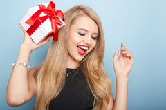 Young woman puts her ear to the present wrapped. Royalty Free Stock Photography