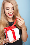 Young woman puts her ear to the present wrapped. Royalty Free Stock Images