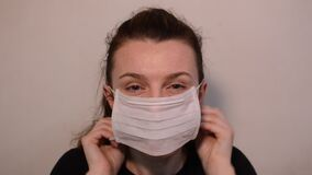 Young woman puts on a medical mask